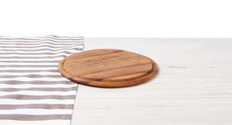 Leeg tafelkleed op houten lijst en pizza scherpe raad die op witte achtergrond wordt ge?soleerd Selectieve nadruk plaats voor voe stock afbeelding