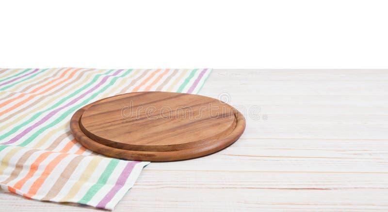 Leeg tafelkleed op houten lijst en pizza scherpe raad die op witte achtergrond wordt ge?soleerd Selectieve nadruk plaats voor voe stock fotografie