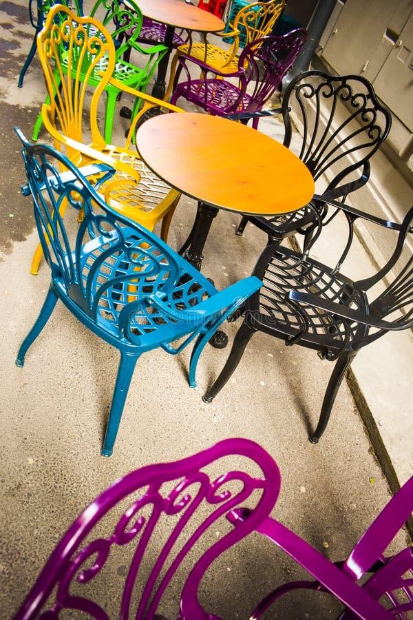Leeg uitstekend terras in historisch de stad in met multi-colored stoelen op de bestratingsstoep Kleurrijke stoelen in retro stock foto's