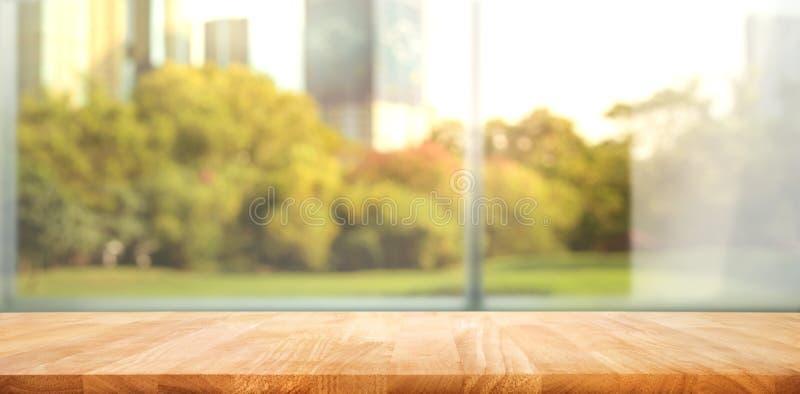 Leeg van houten lijstbovenkant bij het onduidelijke beeld van verse groene tuin met de achtergronden van de stadsstad stock foto's