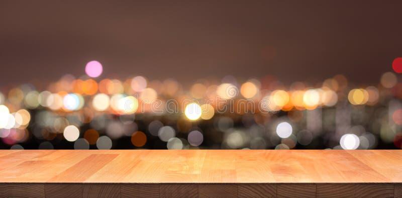 Leeg van witte houten lijstbovenkant op de stad van de onduidelijk beeldnacht, cityscape royalty-vrije stock foto's