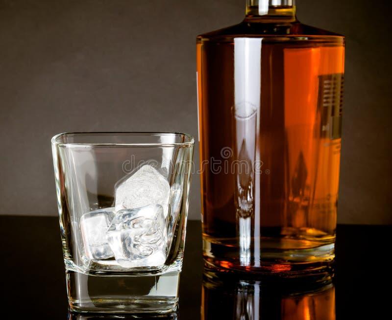 Leeg whiskyglas met ijs dichtbij fles op zwarte achtergrond stock afbeelding