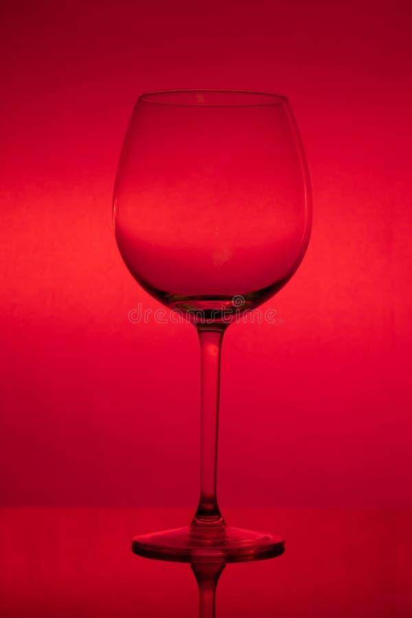 Leeg wijnglas op rode achtergrond, leeg wijnglas stock foto