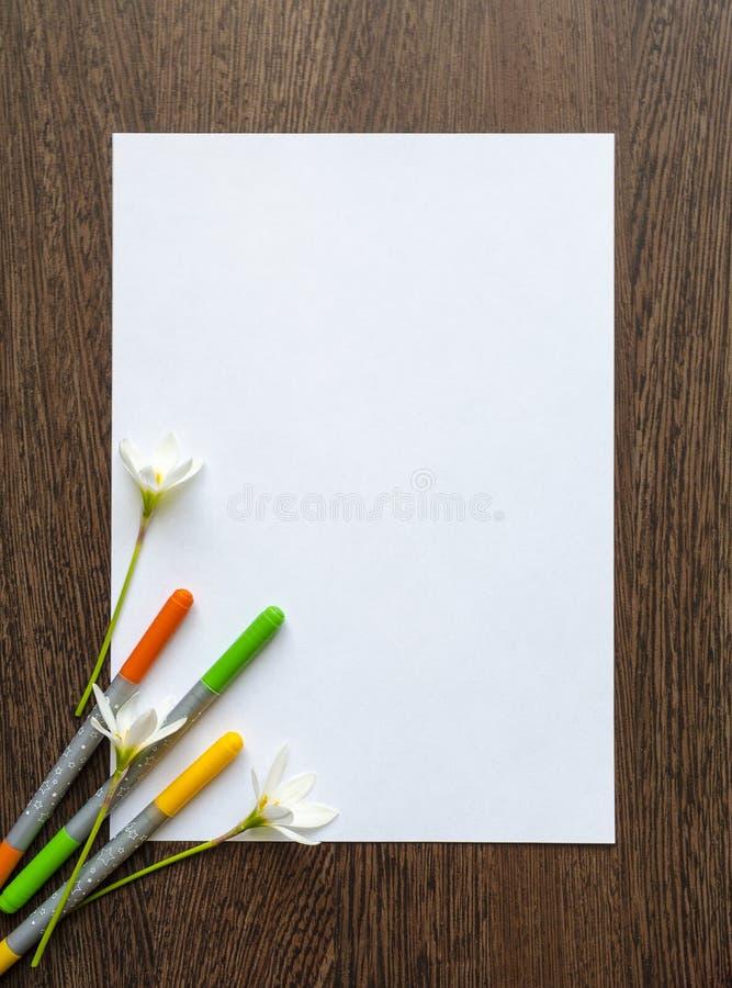 Leeg wit blad van document voor tekst op een donkere houten achtergrond Rond het zijn gekleurde viltpennen en bloemen Model stock foto