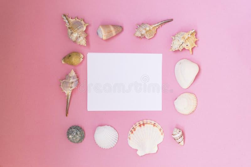 Leeg wit blad van document voor tekst op een roze achtergrond Achtergrond met shells en kiezelstenen stock fotografie