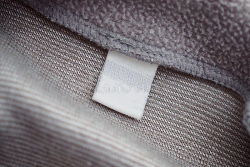 Leeg wit kledingsetiket op de grijze achtergrond van de stoffentextuur stock foto's
