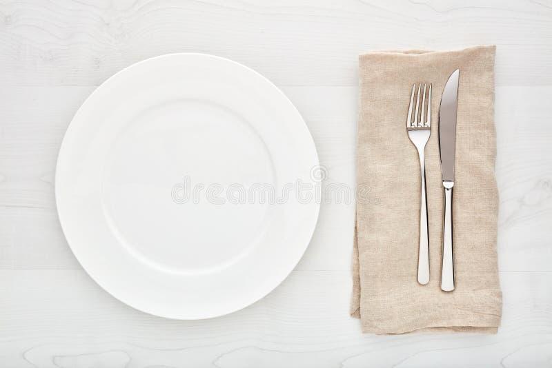 Leeg wit rond ceramisch plaat, vork, mes en servet op witte houten lijst stock afbeelding
