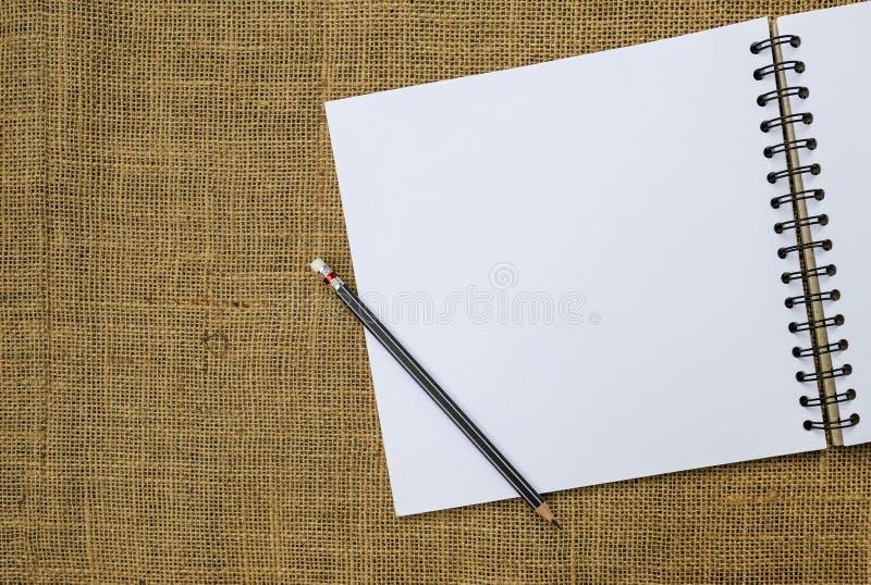 Leeg wit schetsboek en zwart potlood met ruimte op de achtergrond van de jutestof royalty-vrije stock afbeeldingen