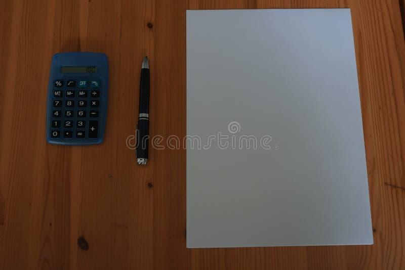 Leeg Witboekblad met pen en calculator op houten bureau royalty-vrije stock fotografie