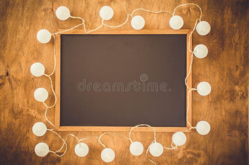 Leeg zwart die bord met witte decoratieve lichten op houten achtergrond wordt omringd stock fotografie