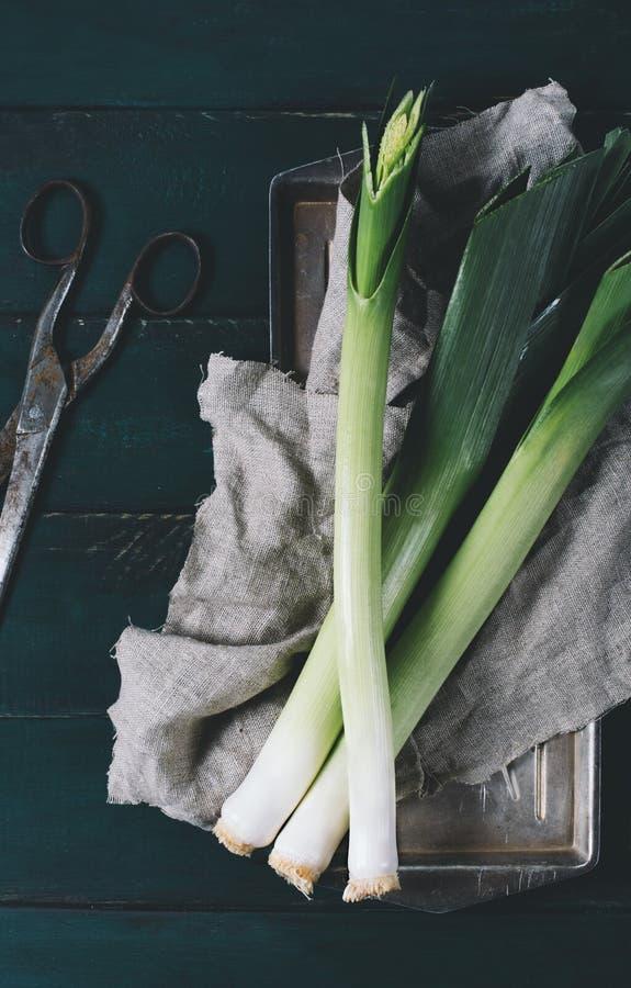 Leek i nożyce na lekkim talerzu na ciemnym tle starzejący się drewnianych desek rocznika pionowo odgórny widok tkaniny i metalu zdjęcia royalty free