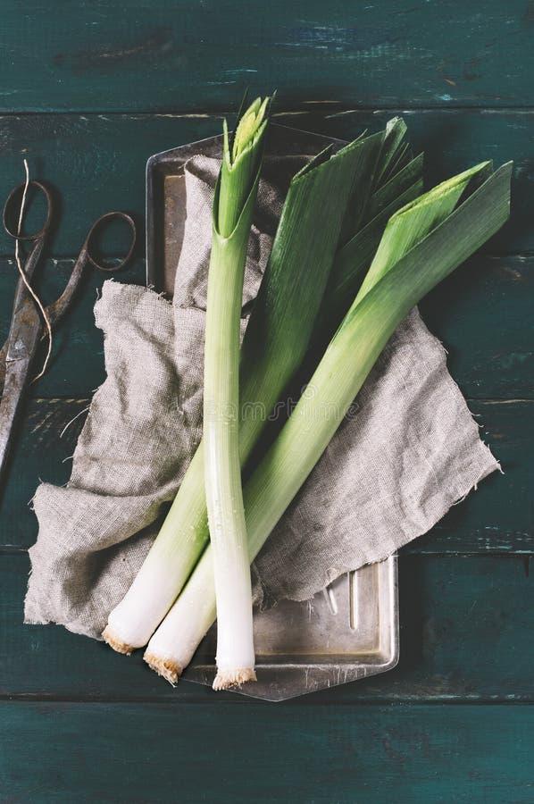 Leek i nożyce na lekkim talerzu na ciemnym tle starzejący się drewnianych desek rocznika pionowo odgórny widok tkaniny i metalu obraz royalty free