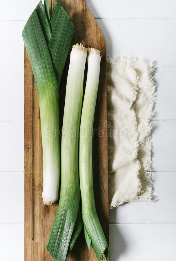 Leek on light textiles and cutting board on a white background the aged wooden planks of vintage vertical top view royalty free stock photo