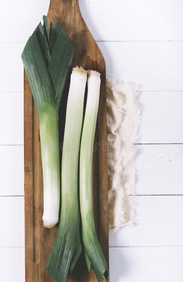 Leek on light textiles and cutting board on a white background the aged wooden planks of vintage vertical top view stock photo
