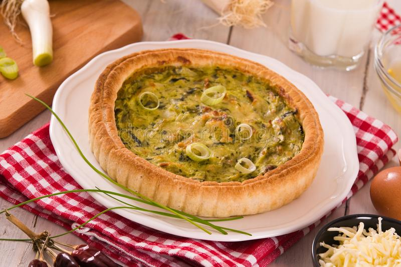 Leek quiche. Leek quiche with cheese on white dish royalty free stock photo