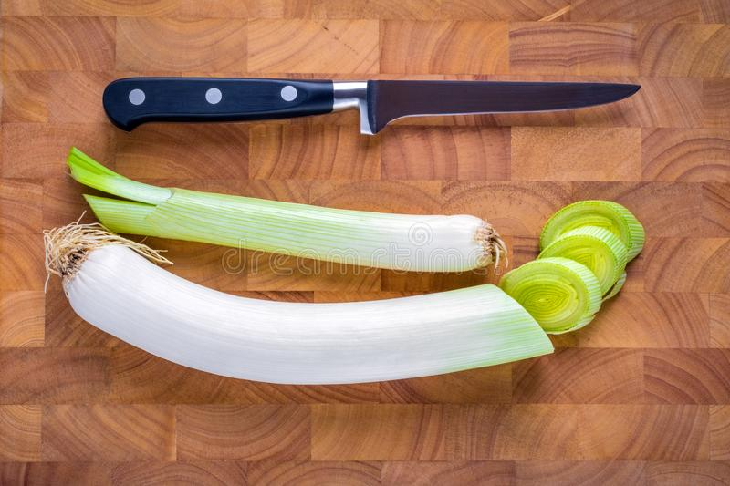 Leek, spring onion and knife on wooden cutting board. With amazing texture stock images