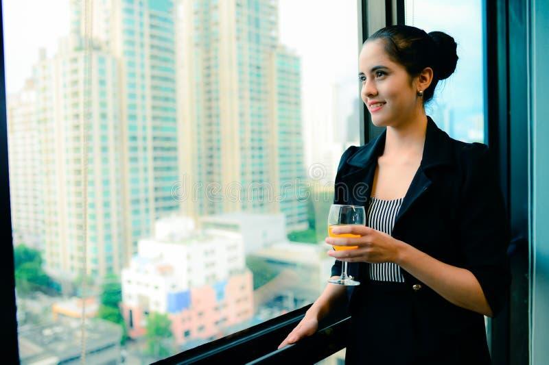Leende av den härliga affärskvinnan på fönstret med champagne, tappningstil royaltyfri bild