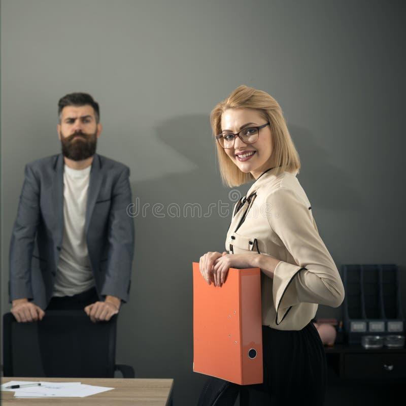 Leende för affärskvinna med skäggig bakgrund för man i regeringsställning Affärskvinnan har skrivbordsarbete för avtal royaltyfri foto