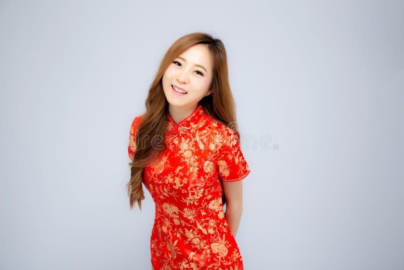 Leende för cheongsam för kläder för kvinna för nytt år för härlig stående lyckligt kinesiskt ungt asiatiskt med gestlyckönskan oc royaltyfri fotografi