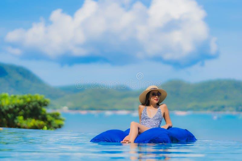 Leende för härlig ung asiatisk kvinna för stående lyckligt att koppla av i simbassäng på stranden för hav för hav för hotellsemes fotografering för bildbyråer