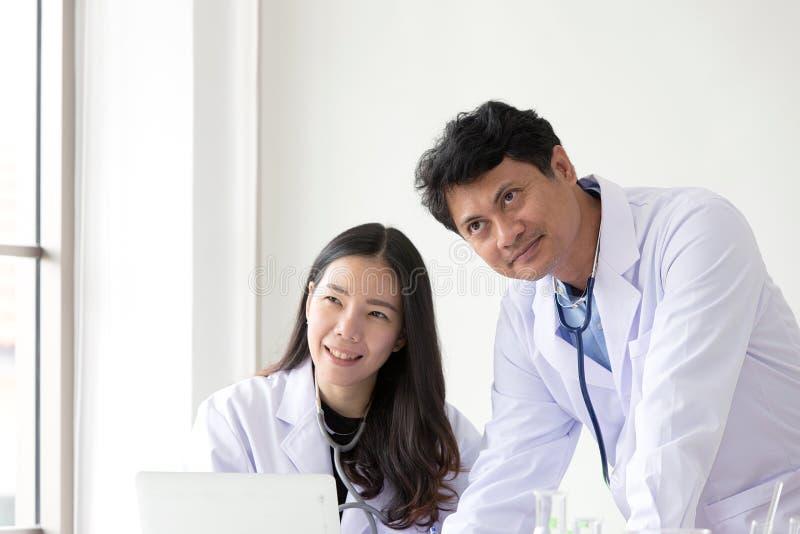 Leende för två asiatiskt medicinska arbetare Stående av den asiatiska doktorn Chemi arkivbild