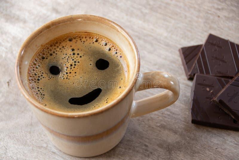 Leende med ett kaffe och några choklader royaltyfri foto