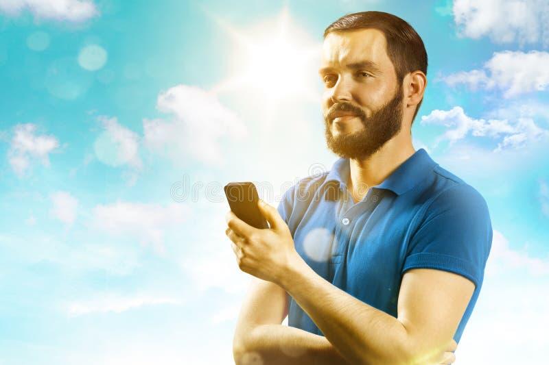 Leende och innehav för ung man en telefon arkivfoto