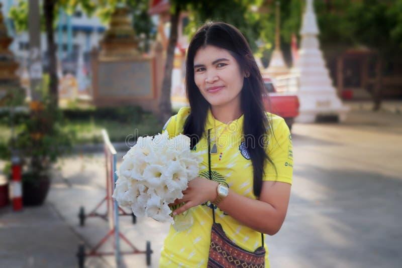 Leendekvinnan att hålla ätliga blommor för ett ätit mål i morgonen på mars 15,2016 parkerar offentligt av Bangkok, Thailand royaltyfri bild