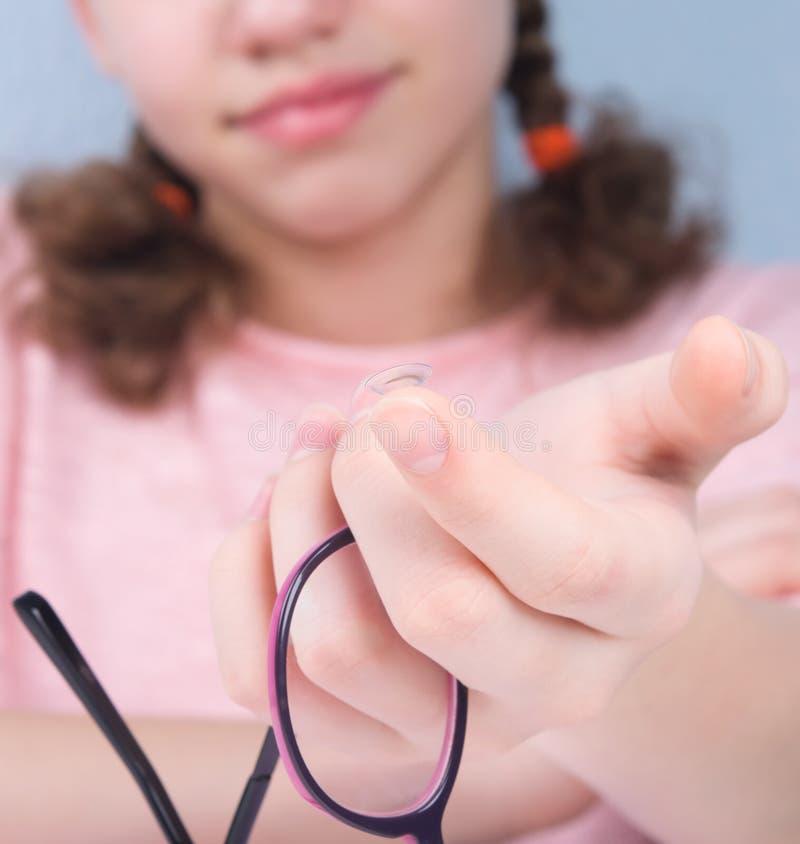 leendet närbilden, hand rymmer ögonexponeringsglas, och det finns en lins på ett finger som förbättrar vision arkivfoton