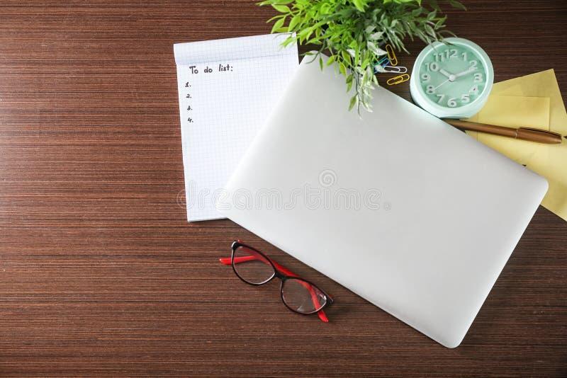 Leer zu-listen Sie mit Laptop und Uhr auf hölzernem Hintergrund auf stockbild