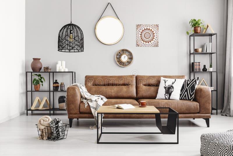 Leerbank met hoofdkussens en deken in elegant woonkamerbinnenland met metaalplanken en moderne koffietafel, stock foto