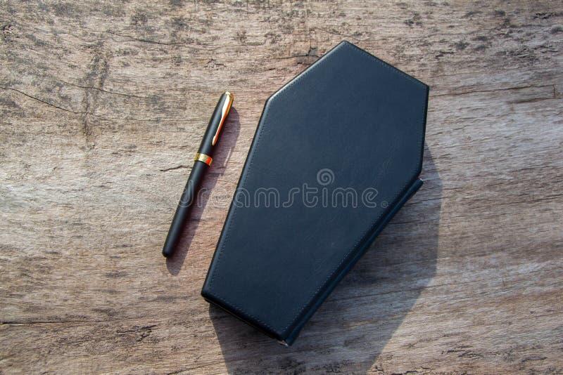 Leerboek in vorm van doodskist, met een potlood op het stock fotografie