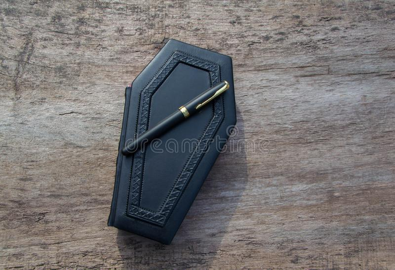 Leerboek in vorm van doodskist, met een potlood op het stock foto