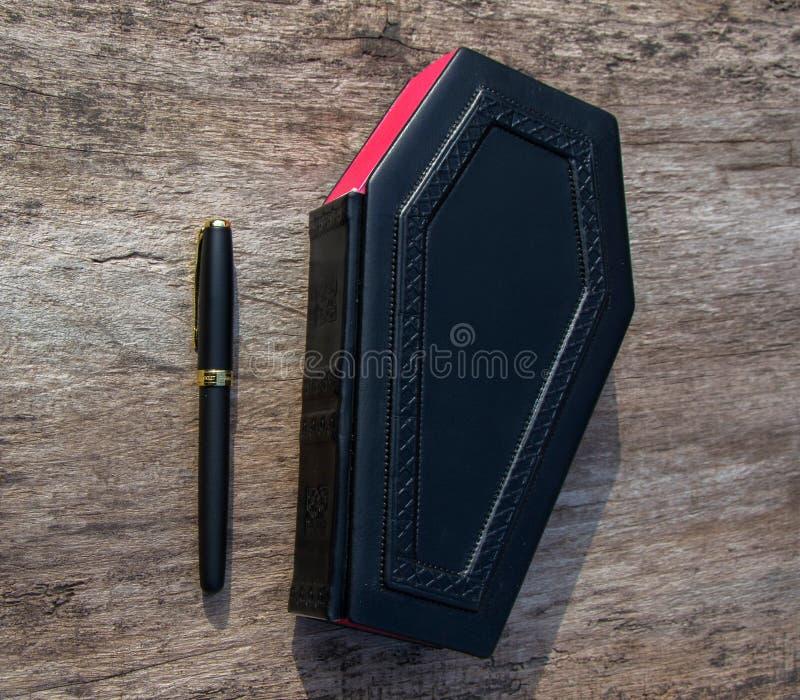 Leerboek in vorm van doodskist, met een potlood op het royalty-vrije stock afbeeldingen