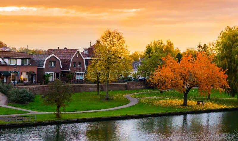 Leerdam Nederländerna som en typisk holländsk stadssikt från parkerar med vatten, väg och gräs på solnedgången i autmunsäsong royaltyfri fotografi