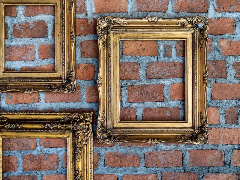 Leere alte aufwändige goldene Rahmen, die an der Backsteinmauer hängen stockbilder