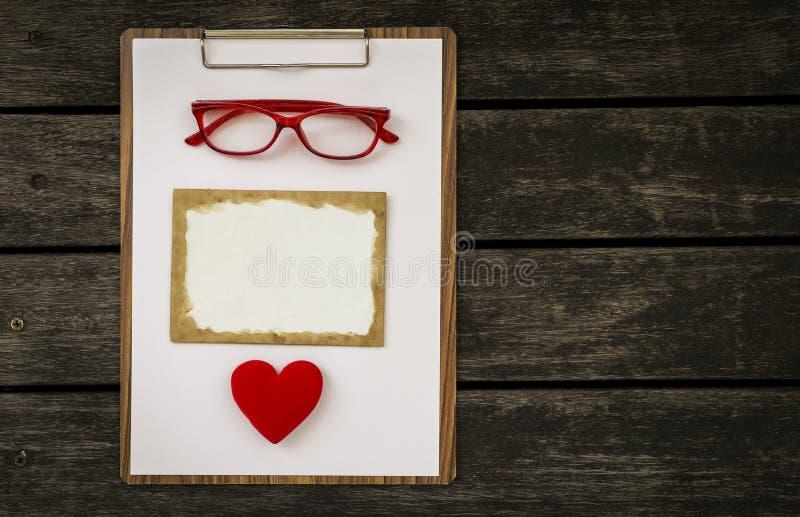 Leere alte Karte mit roten Gläsern und rotem Herzen auf hölzernem Klemmbrett lizenzfreie stockfotos