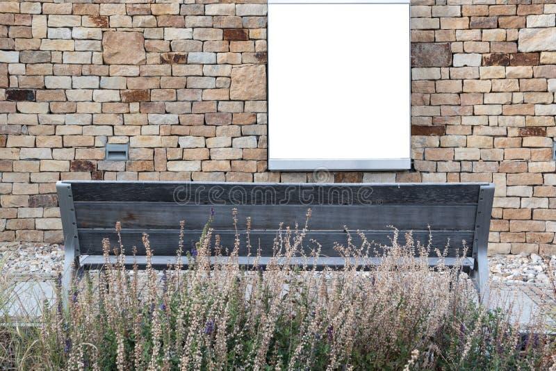 Leere Anschlagtafel auf einer Steinwand und ein banch in der Front und in einem trockenen Gras stockfotos