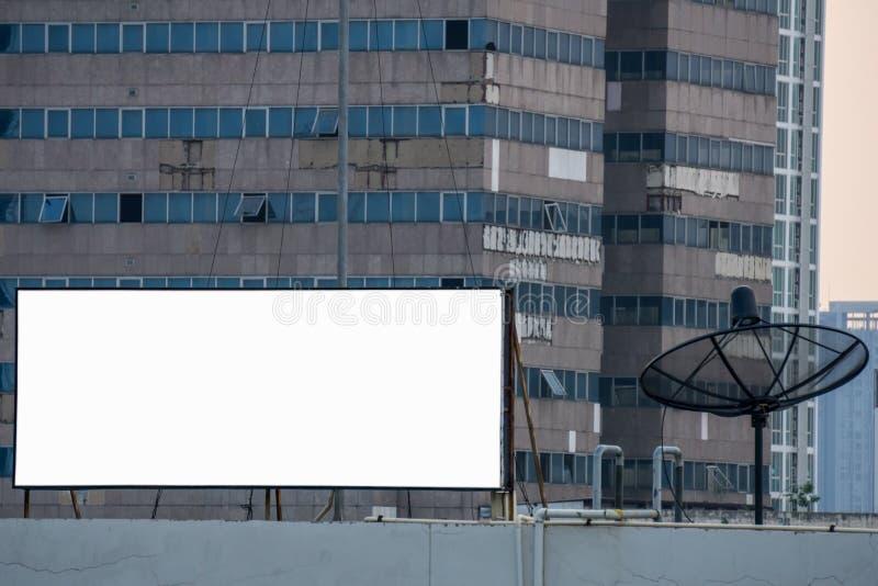 Leere Anschlagtafel und Fernsehsatellitenantenne vor hohem Gebäude stockfoto