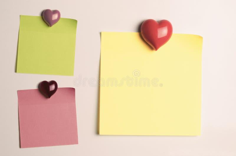 Leere Anzeigen-klebrige Anmerkungen mit Herz-geformten Kühlschrank-Magneten stockbild