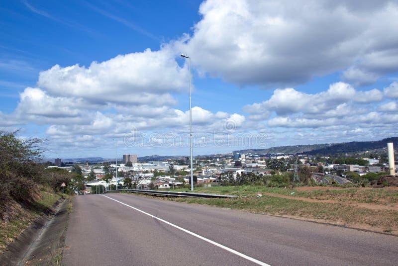 Leere Asphalt-Straße mit Ansicht des Industriegebiets stockfotos