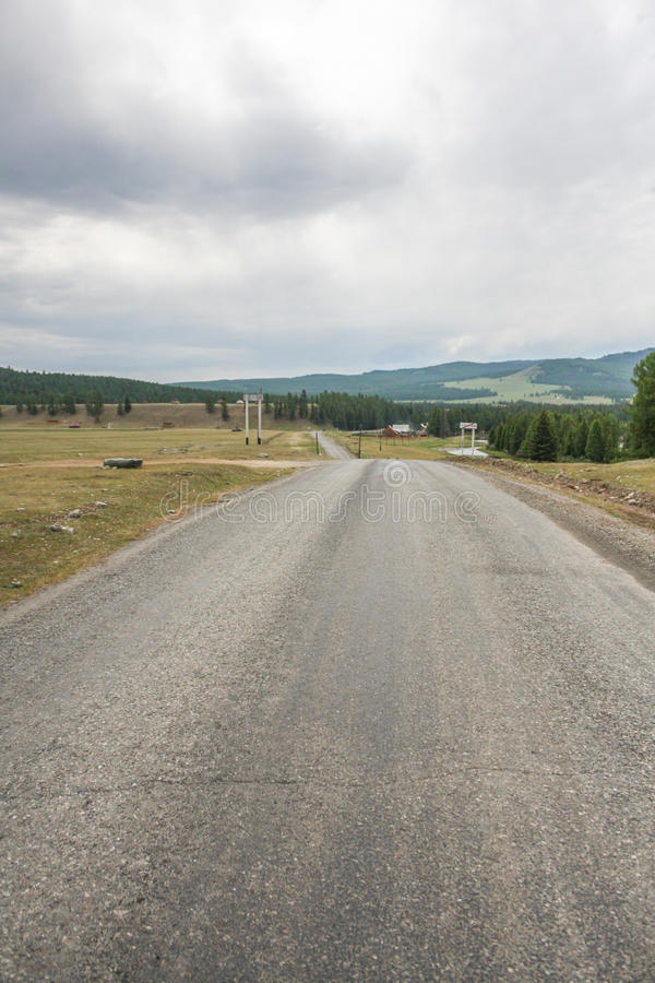 Leere Asphaltstraße, die zu Berge führt stockbilder