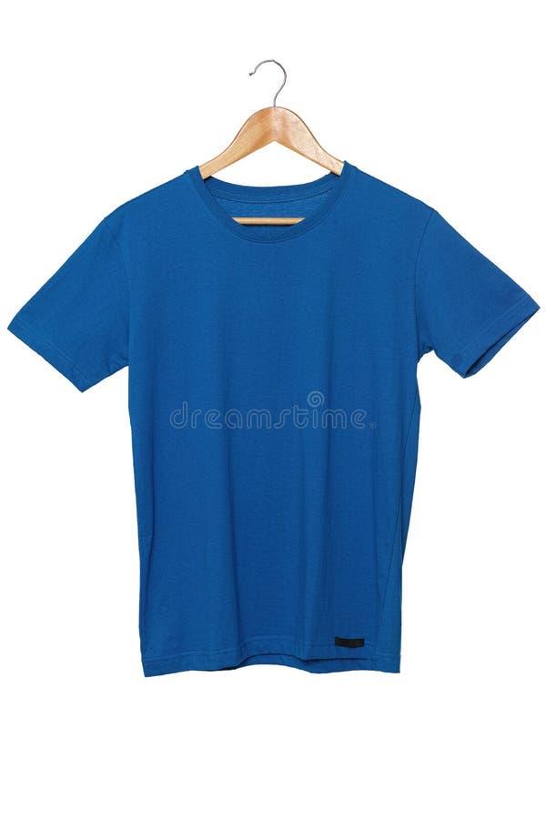 Leere blaue T-Shirts verspotten herauf das Hängen am weißen Hintergrund, der mit Beschneidungspfad auf T-Shirt, Vorderansicht lok stockfotografie