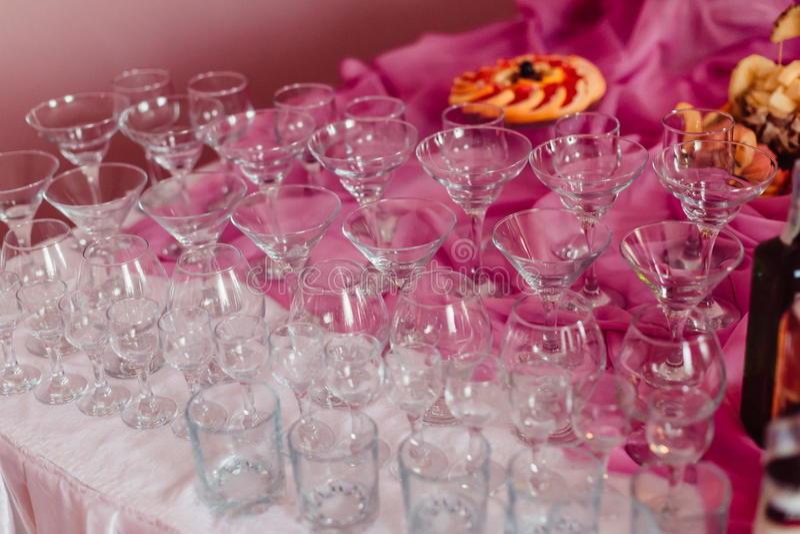 Leere Cocktailgläser stehen auf rosa und weißer Tischdecke stockbild