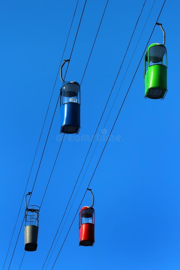 Leere Drahtseilbahnkabinen auf Hintergrund des blauen Himmels stockfoto