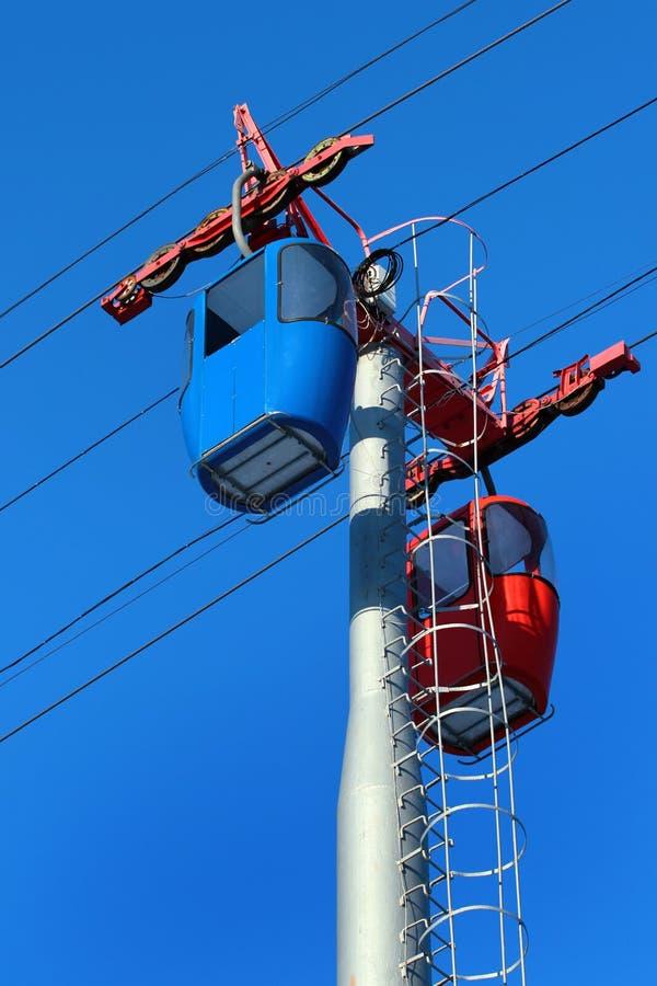 Leere Drahtseilbahnkabinen auf Hintergrund des blauen Himmels stockfotos