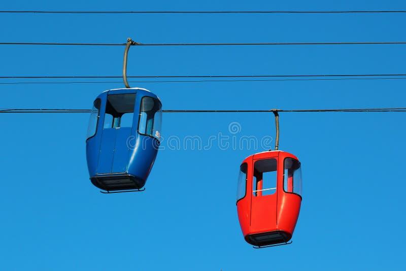 Leere Drahtseilbahnkabinen auf Hintergrund des blauen Himmels stockfotografie