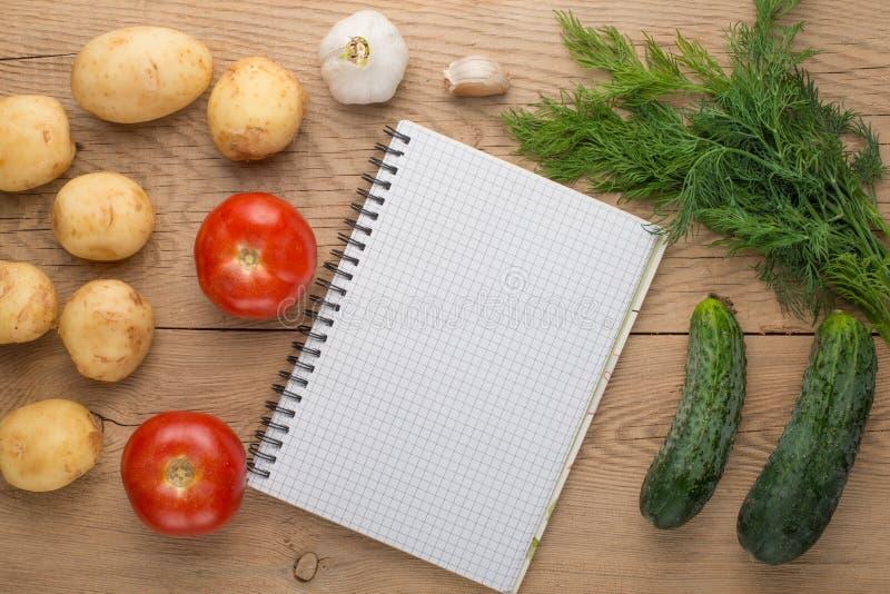 Leere Einkaufsliste auf Papier mit Gemüse auf Holztisch lizenzfreies stockfoto