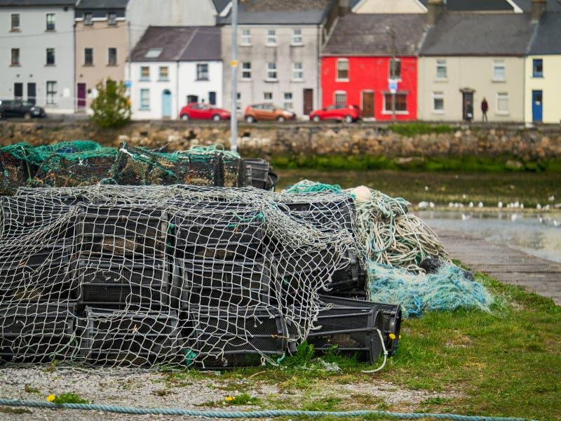 Leere Fischstaplungsfallen, selektiver Fokus, bunte Reihenhäuser im Hintergrund, Galway-Stadt, Claddagh, Irland lizenzfreies stockbild