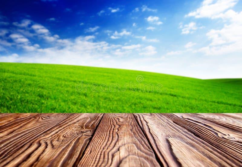 Leere Fliesen an hölzerner tabel Landschaft mit grünem Gras und blauem Himmel mit Wolken auf dem Bauernhof am sonnigen Tag des sc stockbild
